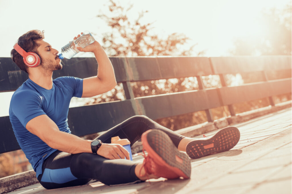 Man drinking some water from a bottle while sitting and resting after training.