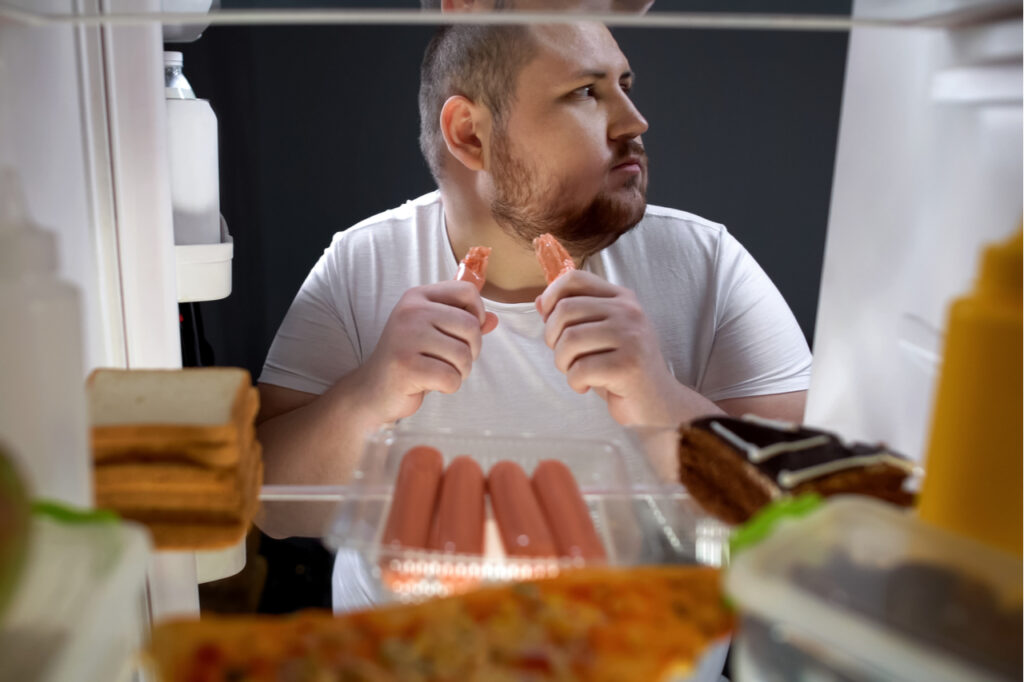 Addicted man secretly eating sausages at night near fridge, unhealthy nutrition.