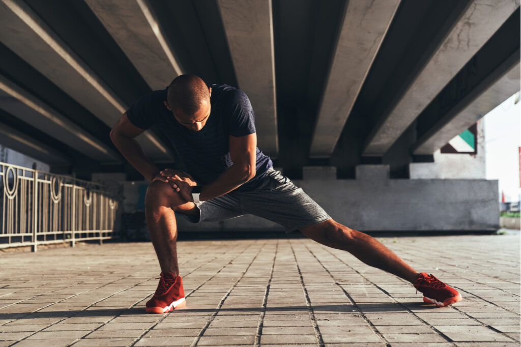 Man in sports clothing stretching while warming up outdoors.