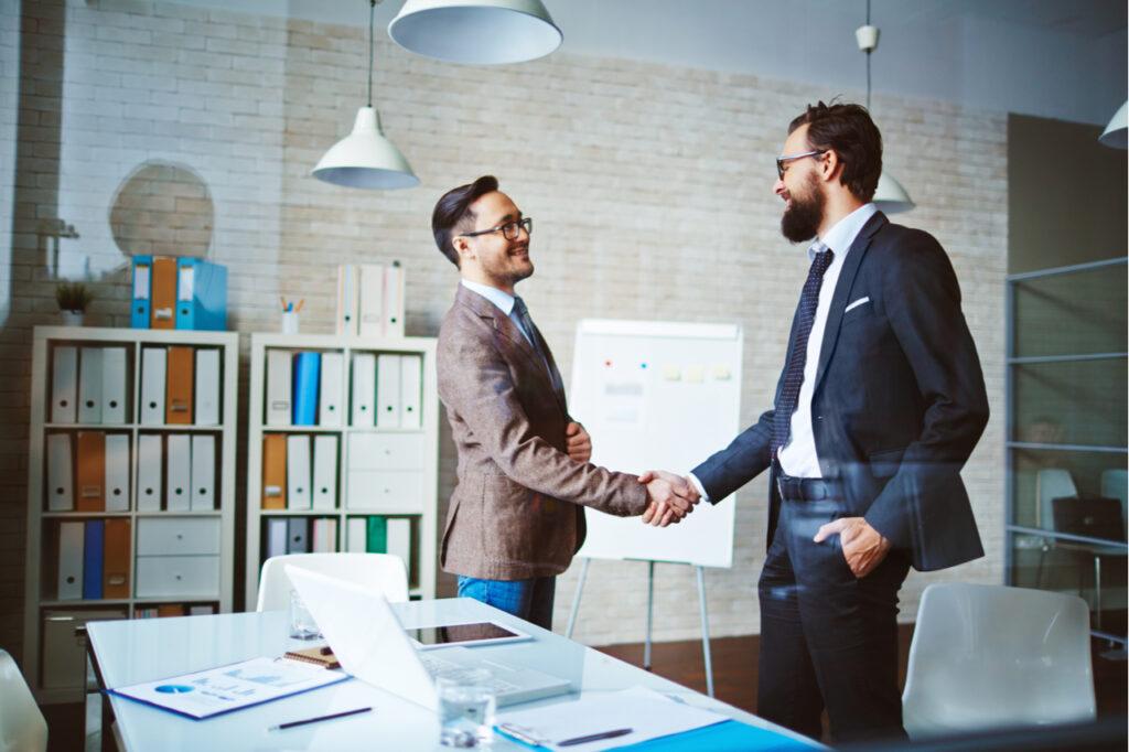 Successful businessmen handshaking after negotiation.