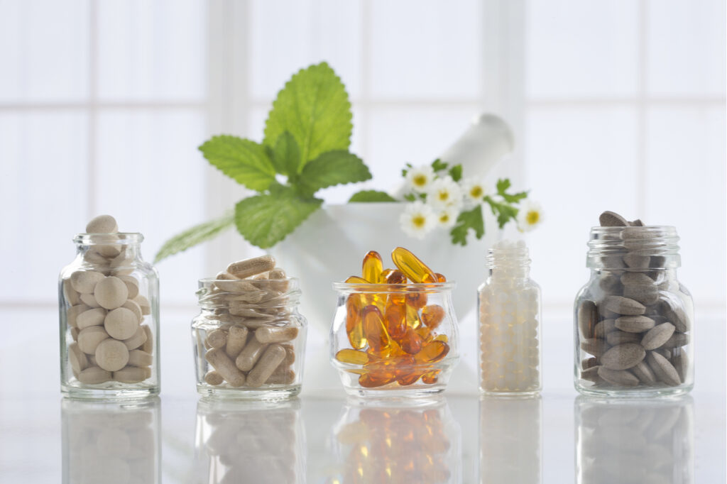 Herbal medicine pills and mortar over bright background.