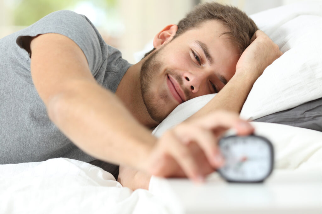 Happy wake up of a happy man lying on the bed and stopping alarm clock.