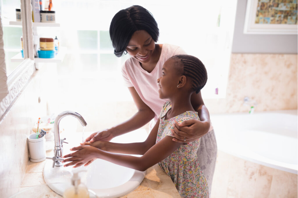 High angle view of mother and daughter washing hands at sink in bathroom.