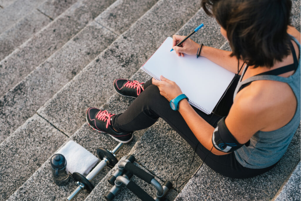 Fitness sporty woman writing on blank notepad while sitting on urban stone stairs before exercises workout routine.