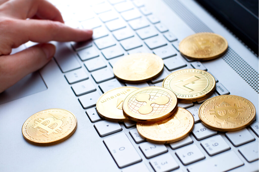 Different types of crypto coins on the computer keyboard close up