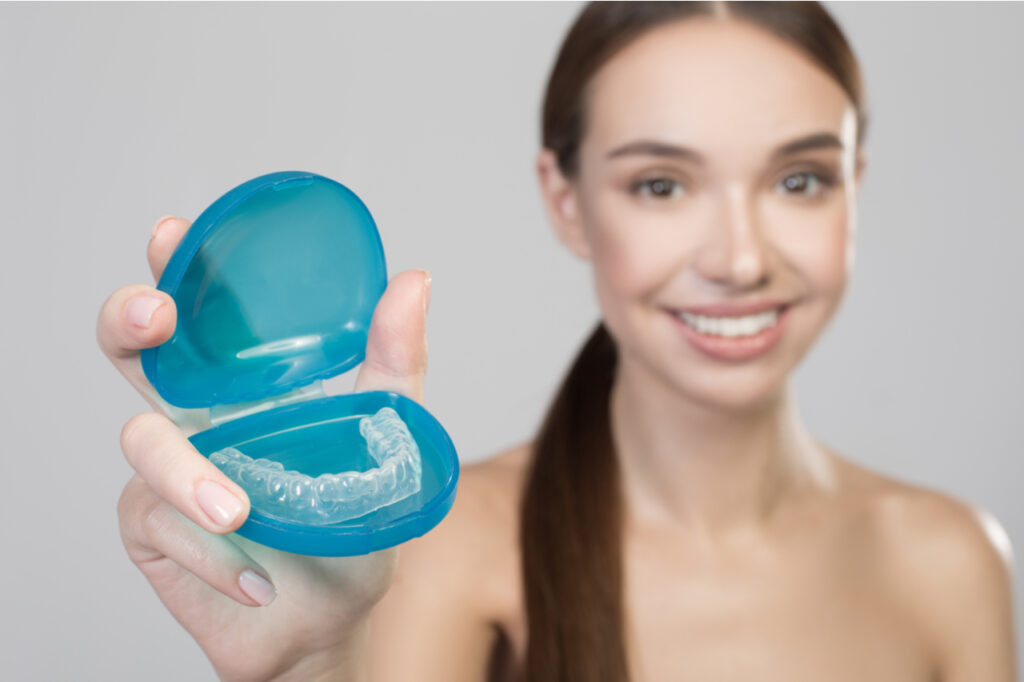 Close up of plastic transparent brace in hand of positive young woman.