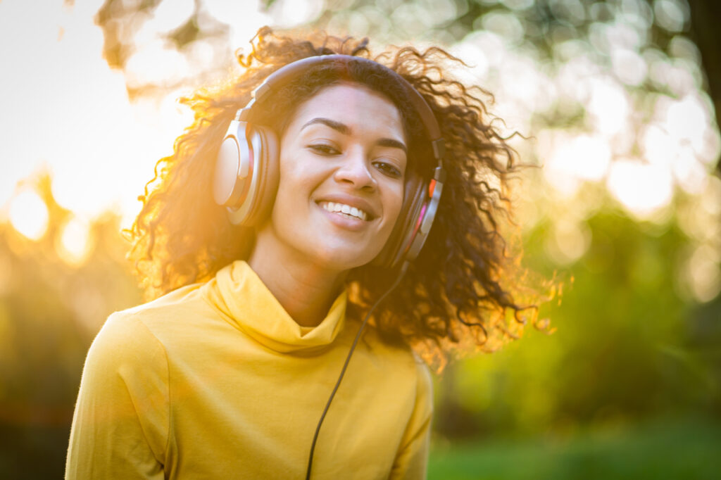 African american woman listing to music showing good emotional health.
