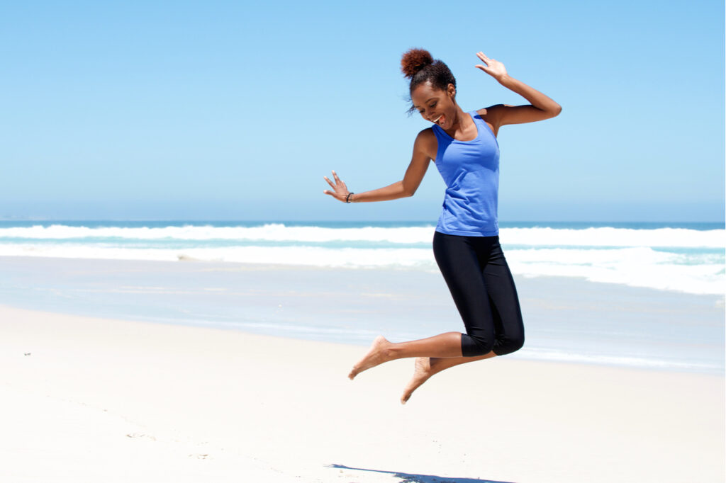 Sporty woman jumping full of energy at the beach.