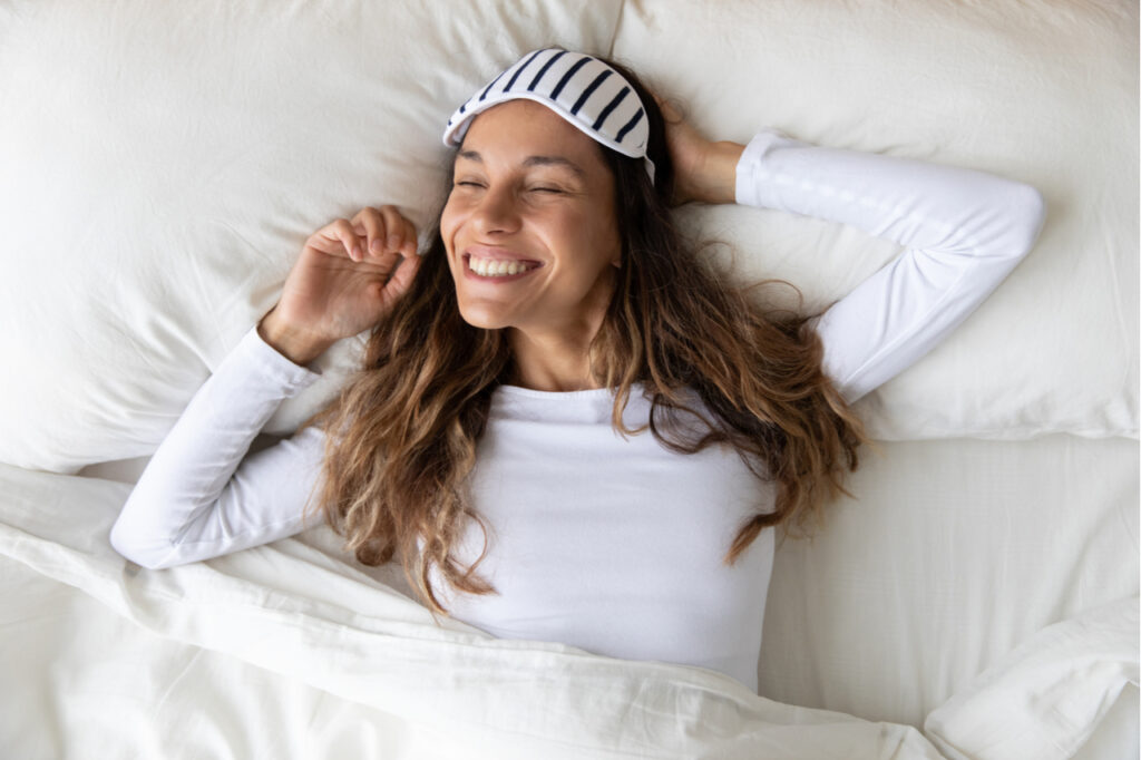 Top view close up woman with healthy smile wearing sleeping mask and white pajamas stretching arms after awakening, feeling fresh, happy beautiful girl lying on soft pillow in comfortable bed
