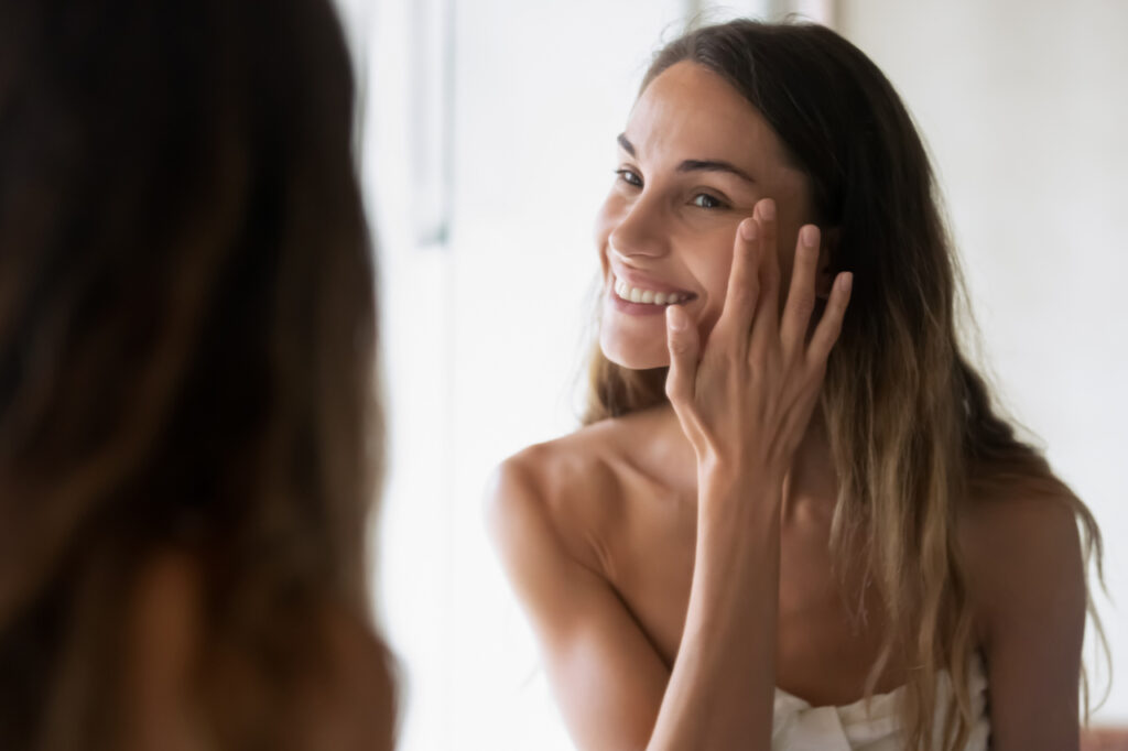Smiling girl in bath towel look in mirror apply moisturizing facial cream or serum, happy young woman perform daily morning skincare face routine for healthy glowing skin, do beauty procedure