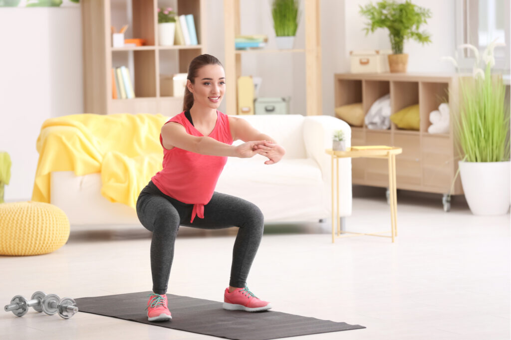 Young woman doing fitness exercise at home.