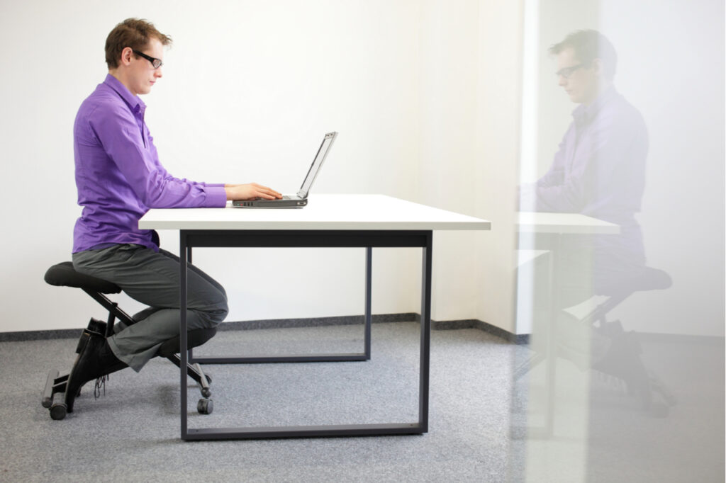 Man in a correct sitting position at workstation.