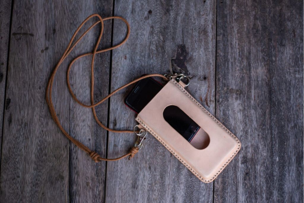 Genuine leather cell phone cover case neck like the iphone 11 case on wood background.