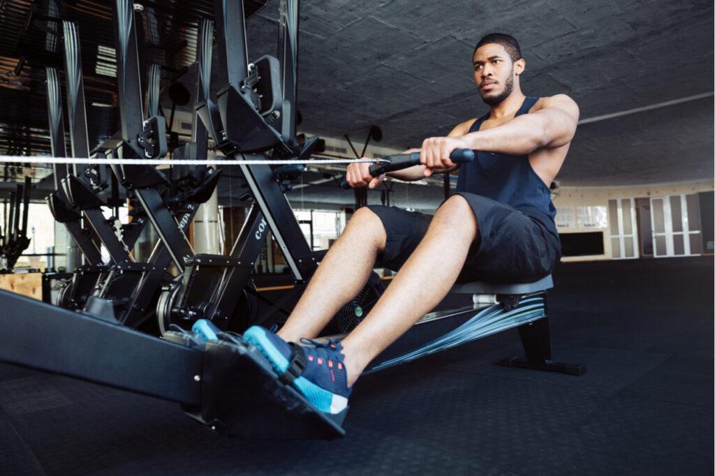 Muscular fit man using rowing machine at gym.
