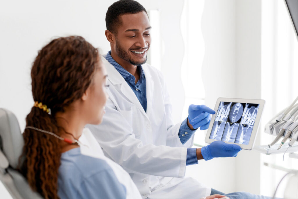 African American dentist and woman patient looking at x-ray picture on digital tablet at clinic