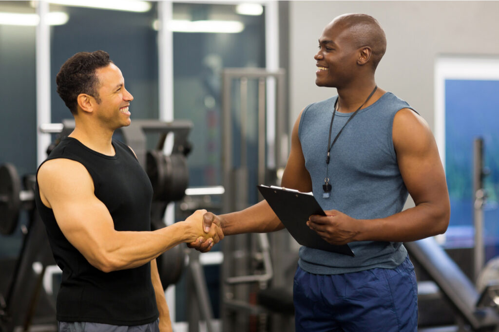 Friendly personal trainer shaking hands with a client.
