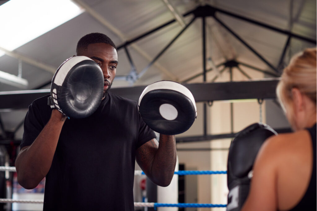 Male personal trainer sparring with female boxer in the gym.