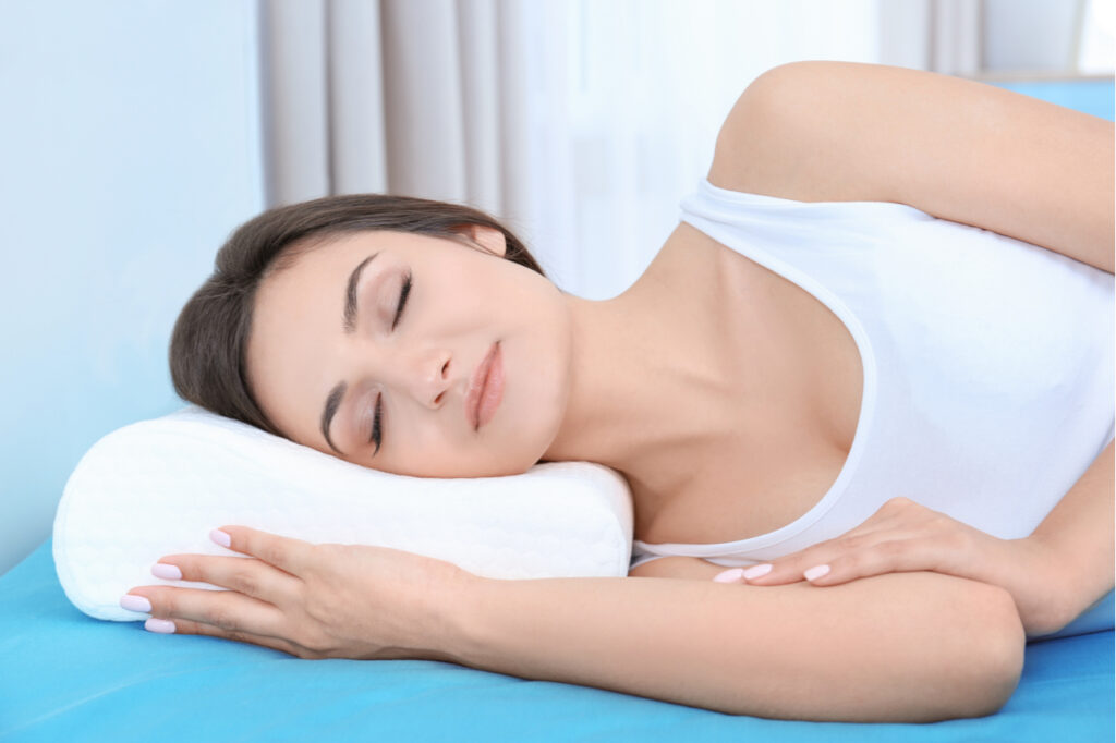 Woman sleeping on bed with orthopedic pillow at home.
