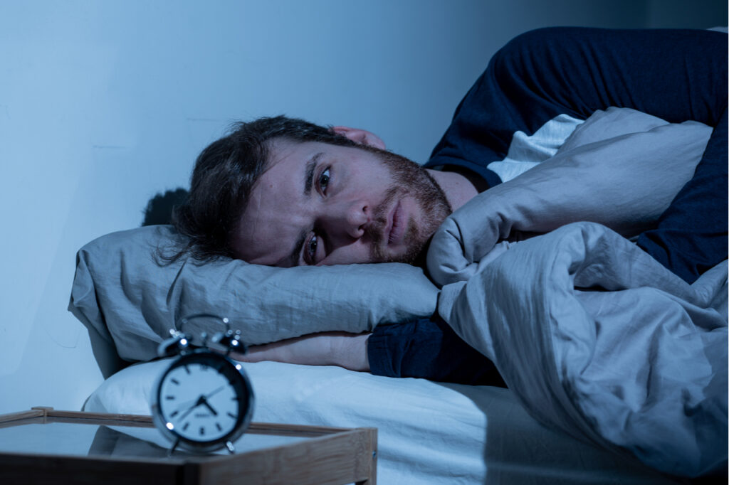 Sleepless and desperate man awake at night not able to sleep.