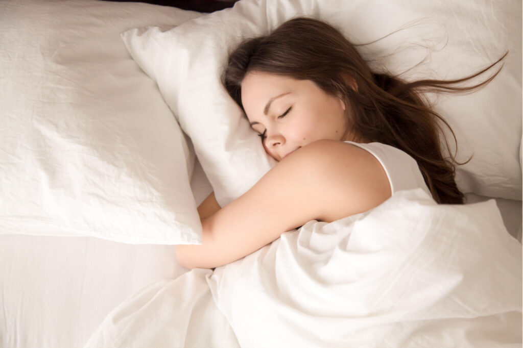 Woman sleeping well in bed hugging soft white pillow aiming for good posture.