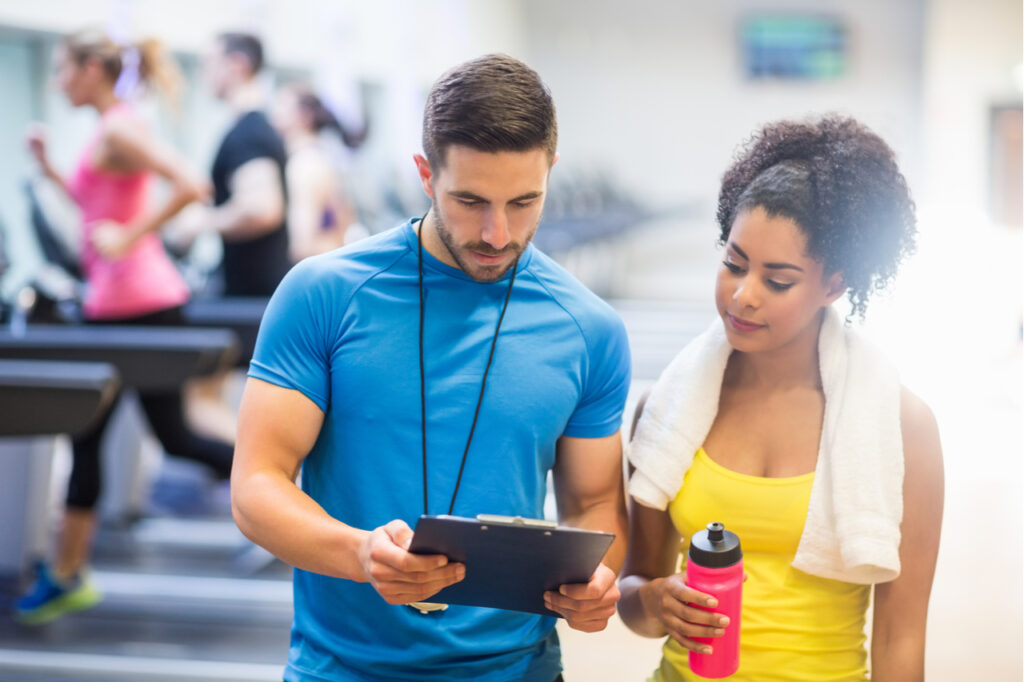 Fit woman talking to her trainer at the gym.