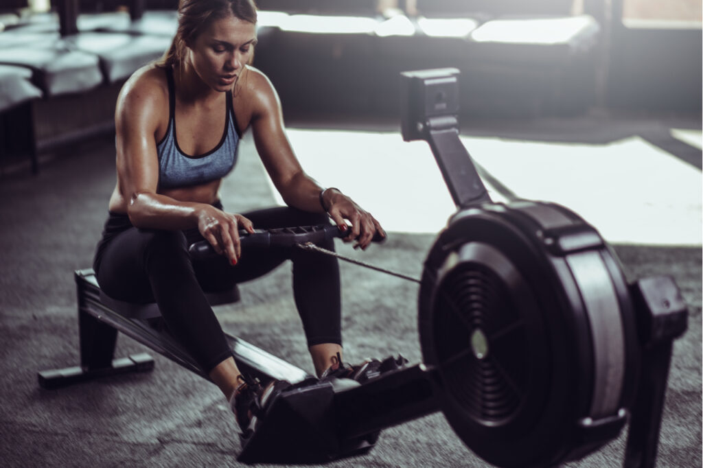 Young female athlete using rowing machine