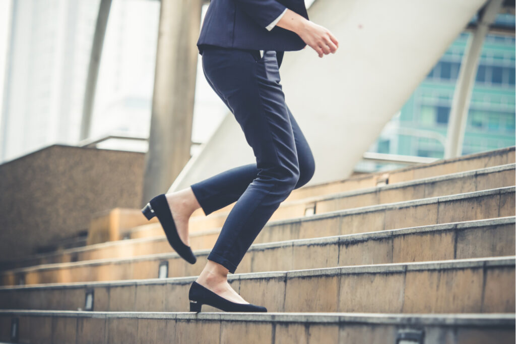 Close up legs of businesswoman fitness snacking walking stepping up stair in modern city.