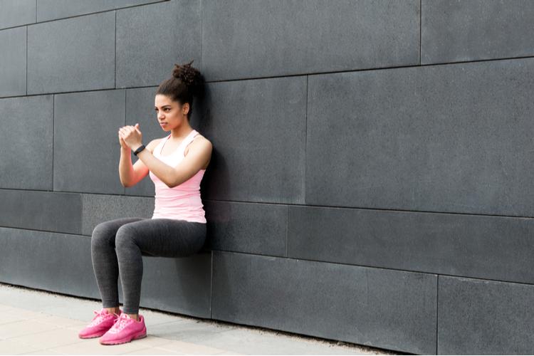 Athlete doing wall squat on city street.