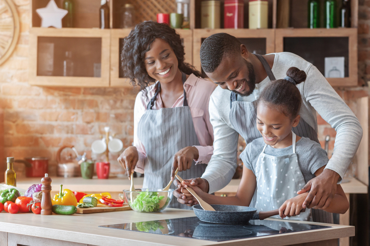Parents teaching their adorable daughter how to cook healthy food.
