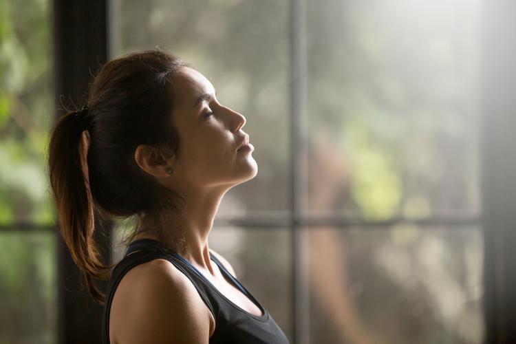 Yogi woman breathing fresh air with eyes closed.