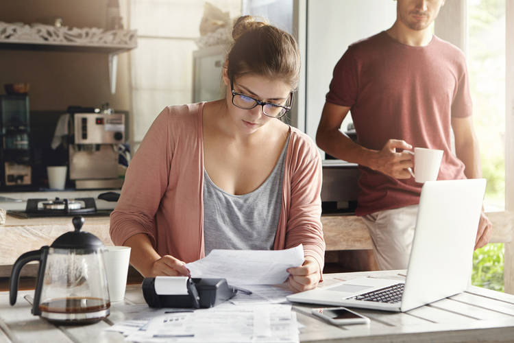 Young woman doing accounts together with her husband at home, budgeting.