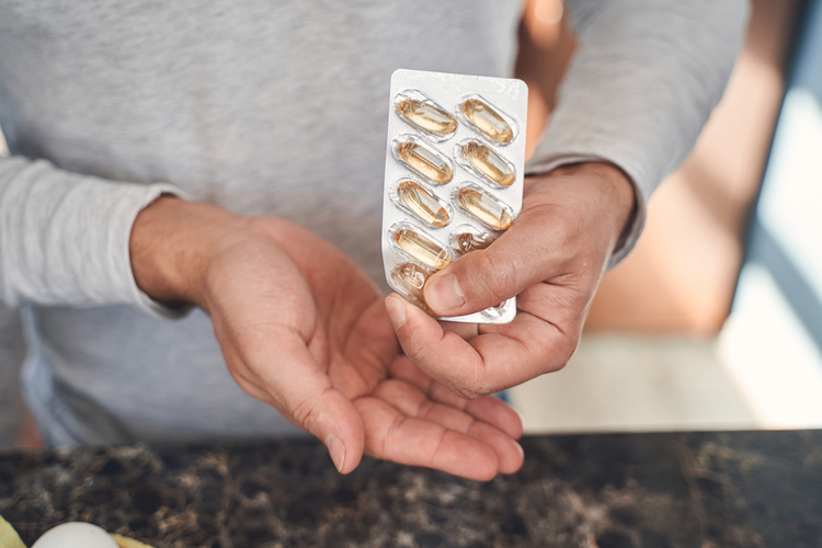 Man taking a gel capsule from a blister pack.