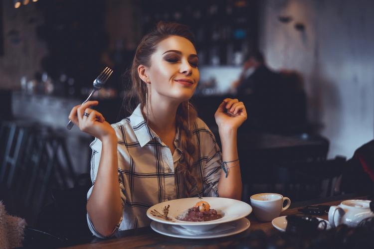 Woman enjoying her dinner in a restaurant.