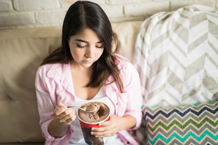 Woman depressed eating chocolate ice cream.