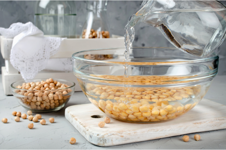 Chickpea soaked in water in a glass bowl.