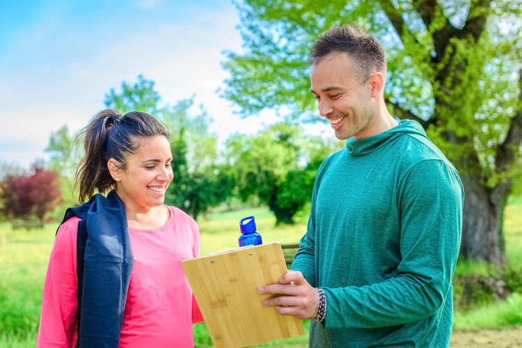 A young woman talking to her personal trainer about her fitness goals and achievements.