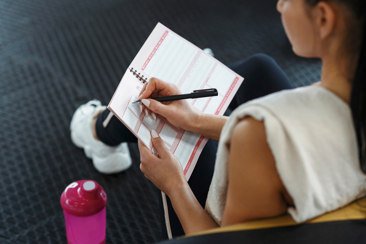 Workout planning. Young woman making her workout schedule in notebook indoors, above view