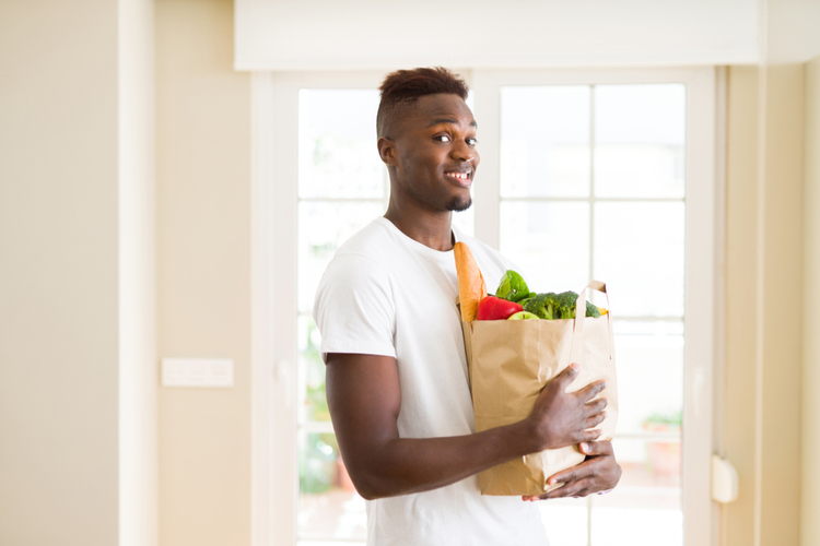 Man holding paper bag full of healthy choices groceries as part of how to stop emotional eating.