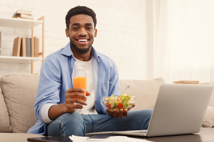 Man eating healthy lunch and watching movie on laptop at home.
