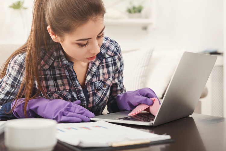 Woman cleaning laptop keyboard.