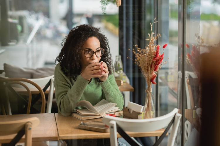 Woman in eyeglasses and book drinking coffee in cafe