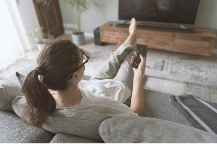 Woman relaxing on the sofa at home and holding a remote.