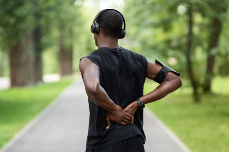 Man in sportswear standing in park and touching injured back needing abdominal exercises.
