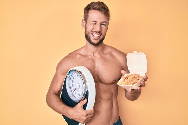 Man shirtless holding weighing machine and fried potatoes winking during mental health awareness month.
