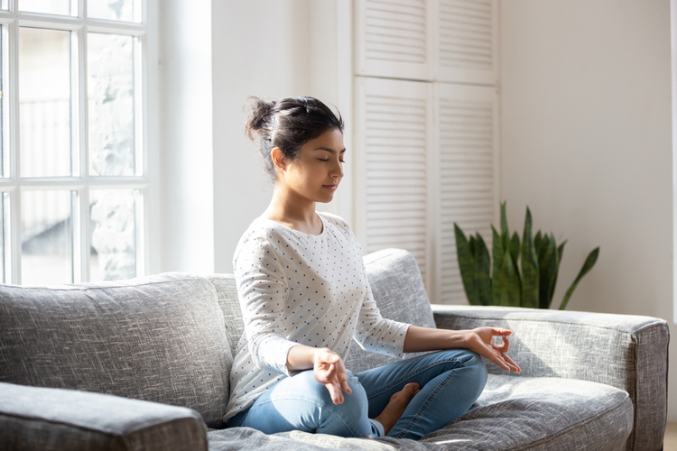 Female sitting on couch lotus pose put hands on lap folded fingers closed eyes.