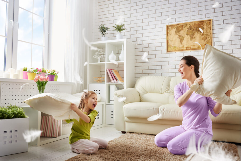 The mother and her child girl are fighting pillows.