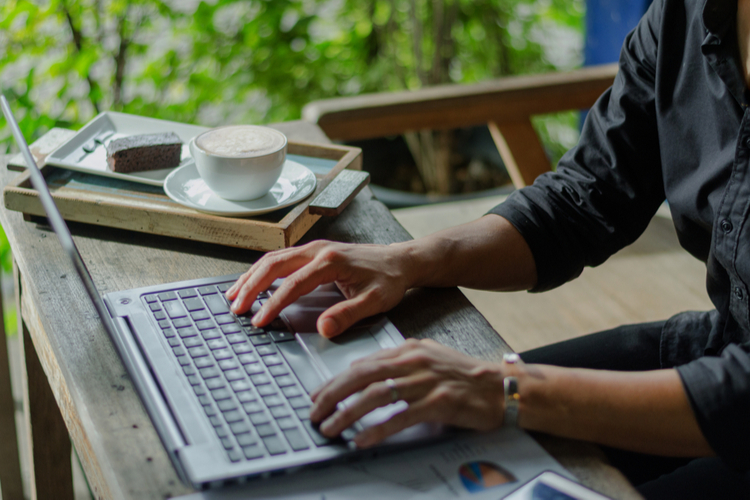 Freelancer using laptop computer working on part-time job while drinking coffee.