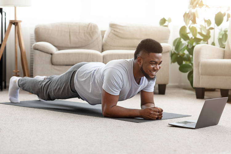 Man doing yoga plank while watching online tutorial on laptop.