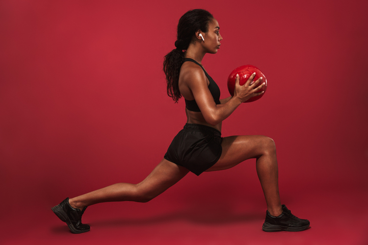Woman doing sport lunges exercises with ball.