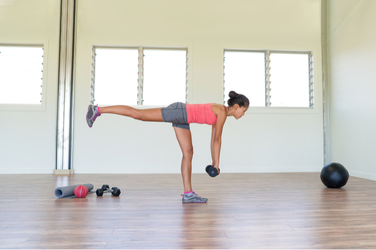 Woman strength training at gym exercising hamstring and lower back muscles with single-leg deadlift exercises.